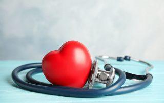 Ein Stethoskop liegt aufgerollt auf einem türkisen Untergrund, das Bruststück berührt ein klassisches, rotes Herz.